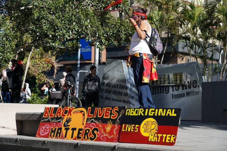 Una persona habla en el escenario de Black Lives Importa protesta en Australia.