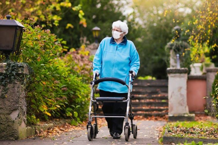 Una anciana con una máscara camina con un marco en un jardín.