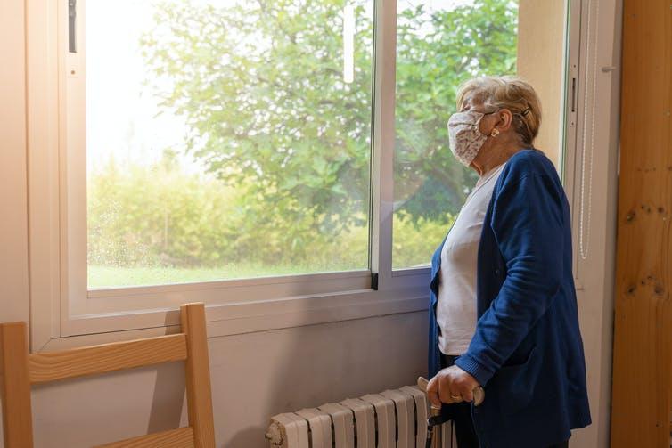 Una anciana con una máscara mira por la ventana.